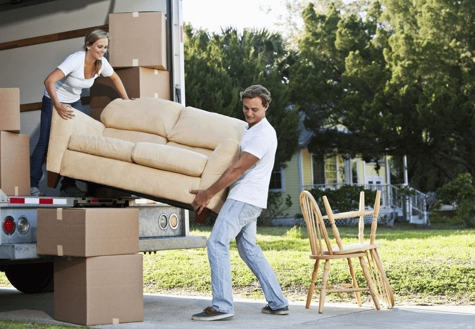 a man and woman unloading a couch from a moving truck