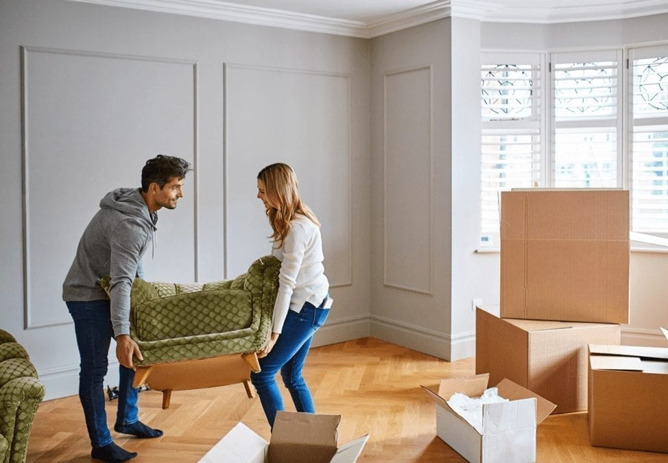a man and woman moving furniture