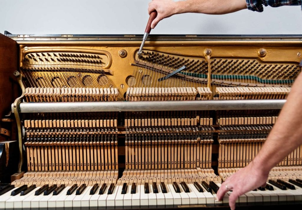 a piano tuner working on an upright piano