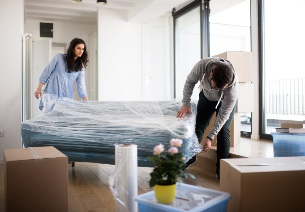 a couple wraps their furniture and packs boxes to place in climate-controlled storage