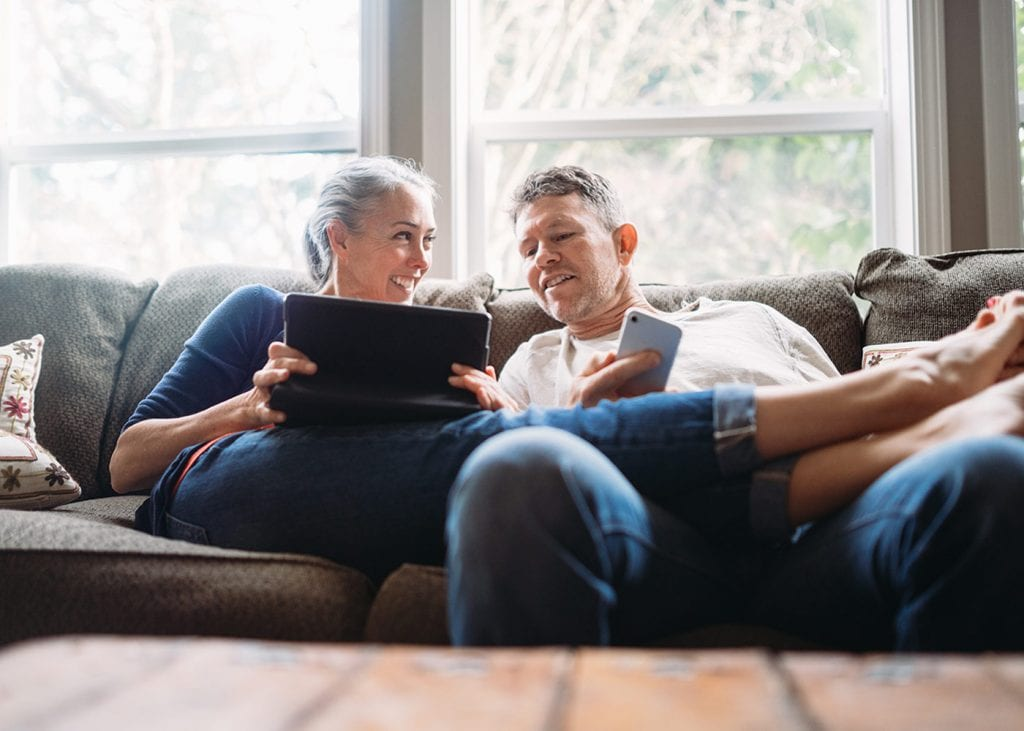 couple sitting on couch with tablet and iphone