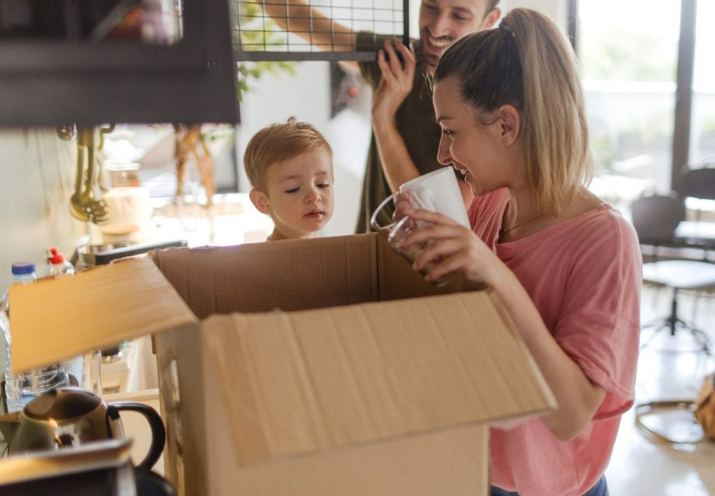 A young family packing dishes in a moving box