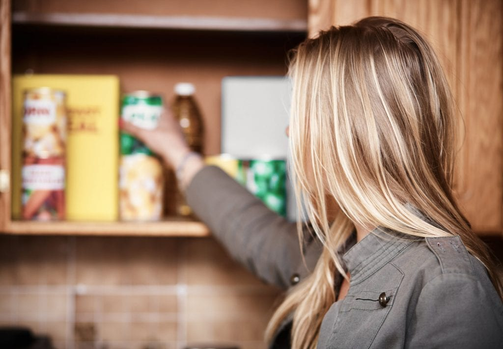 A woman taking a can of food out of the pantry