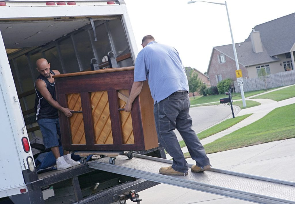 men moving a piano onto a moving truck