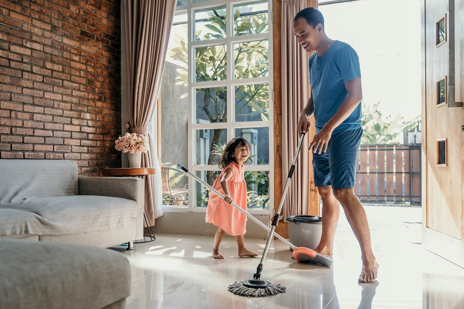 Man and daughter spring cleaning during coronavirus