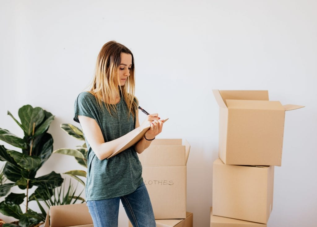 woman making list while packing and moving