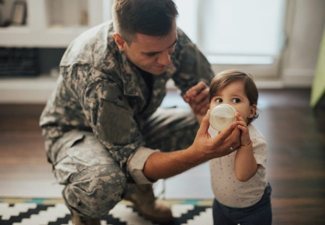 military soldier feeding his baby