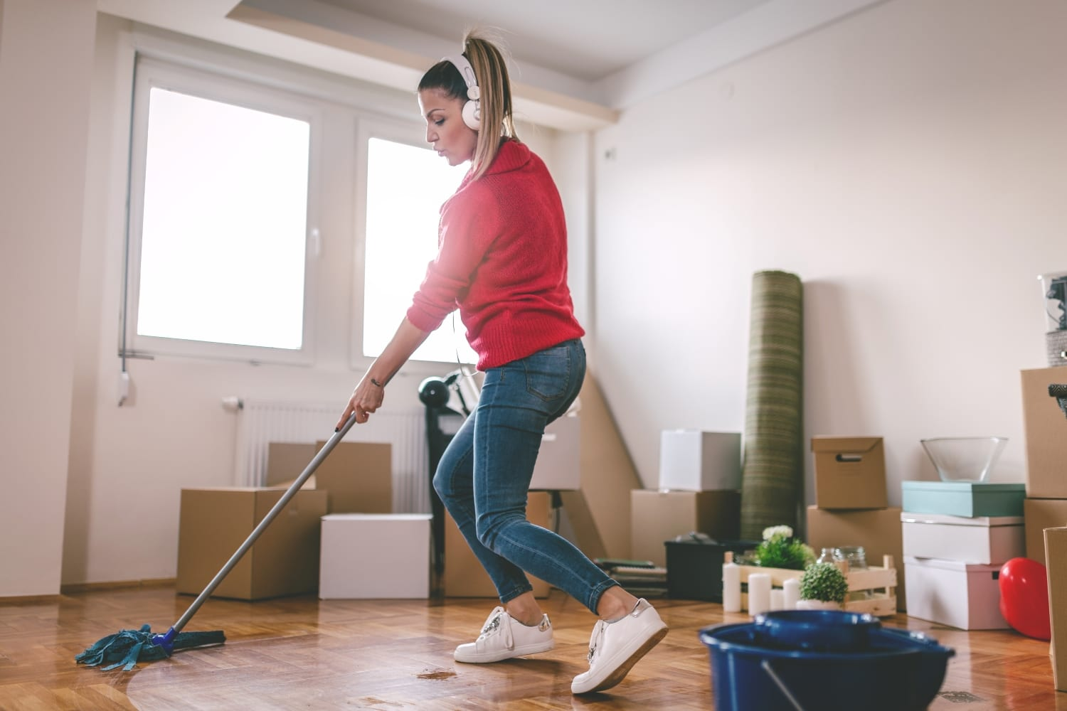 a woman cleaning her apartment before moving out so she can get her deposit back