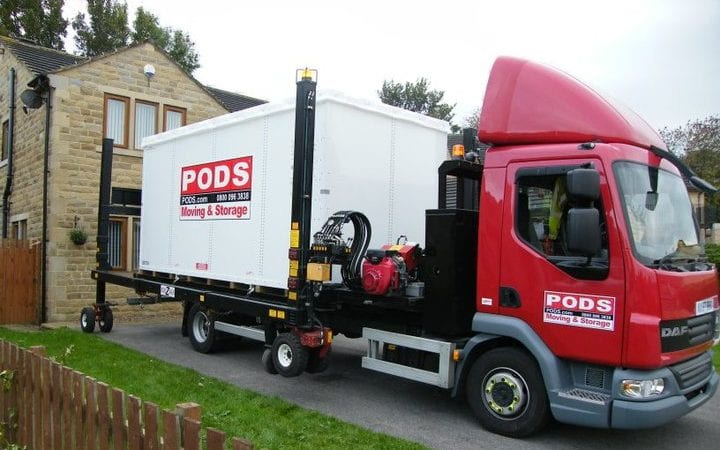 PODS Moving & Storage truck delivering a portable storage container