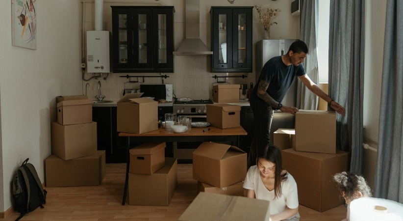 a young family packs boxes preparing to move