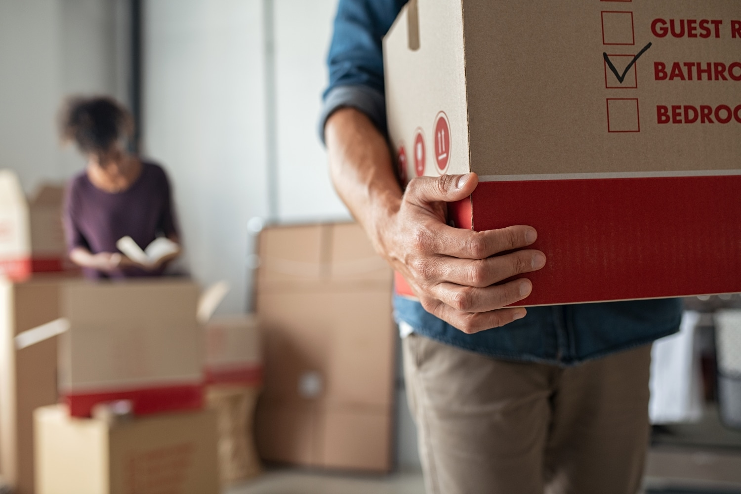 man carrying moving box while woman is packing