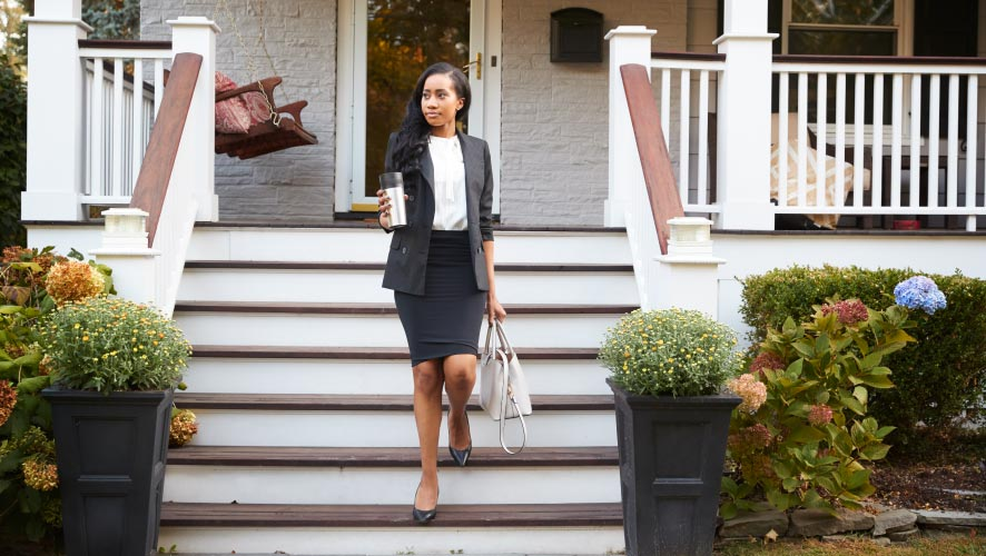 Business woman walking down porch stairs leaving home for work