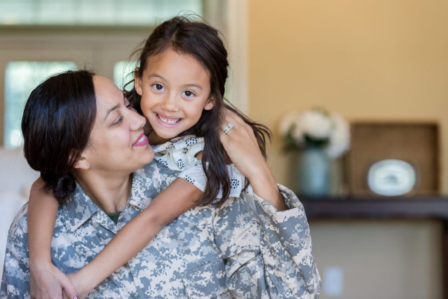 A military woman holding her daughter