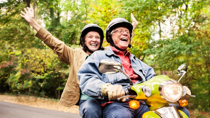 A happy retired couple riding on a moped