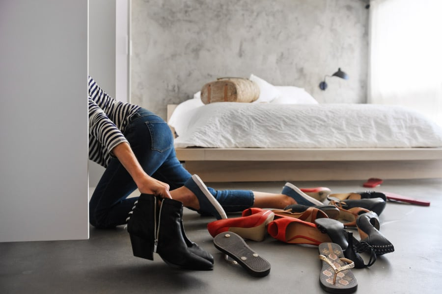 A woman trying to find a spot for her shoes in her closet