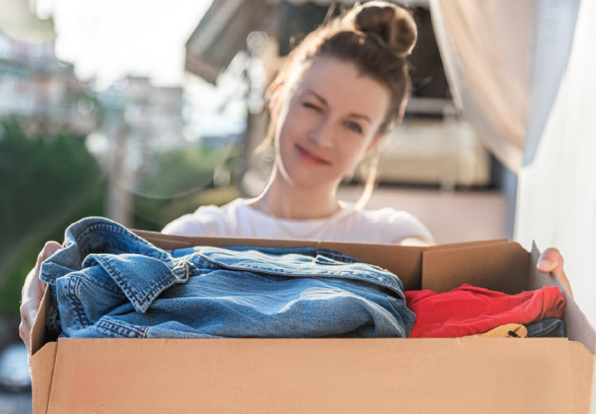 A woman holding a box of clothing donations after decluttering her house