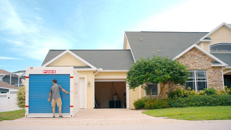 Homeowner opening a PODS moving and storage container in front of a suburban home