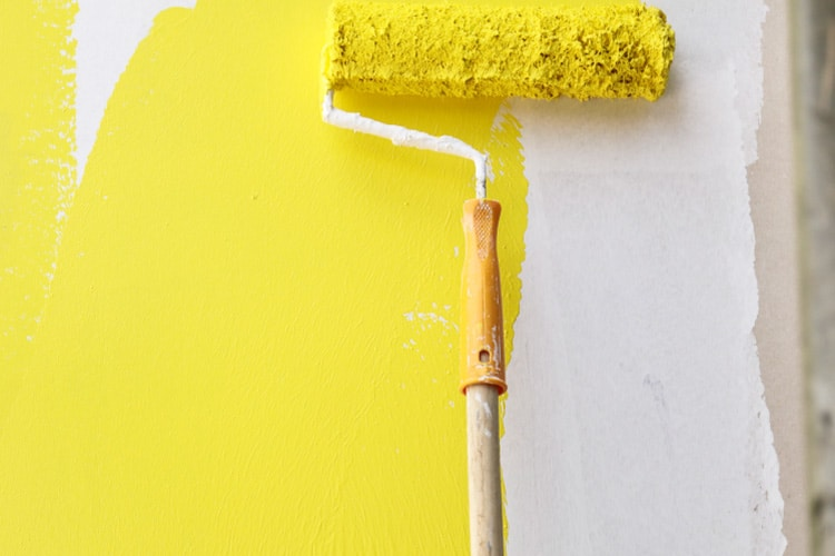 Painting a wall yellow during a home renovation