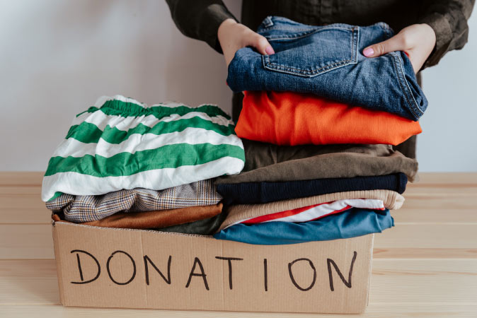 Someone donating their clothes while packing
