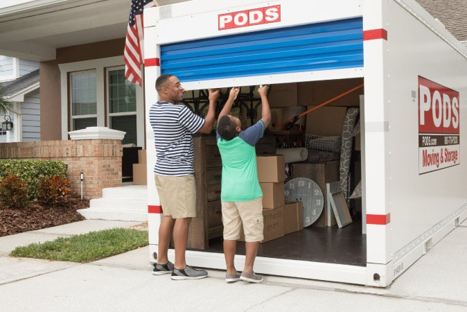 A man and his son opening the door on their PODS moving and storage container